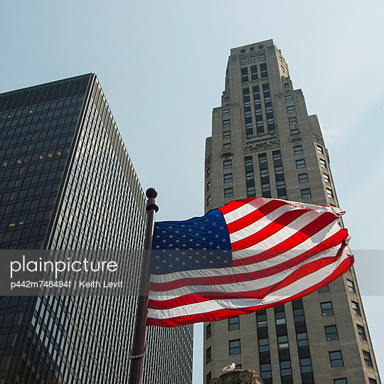 An American Flag Flying In Front Of Skyscrapers; Chicago Illinois United States Of America