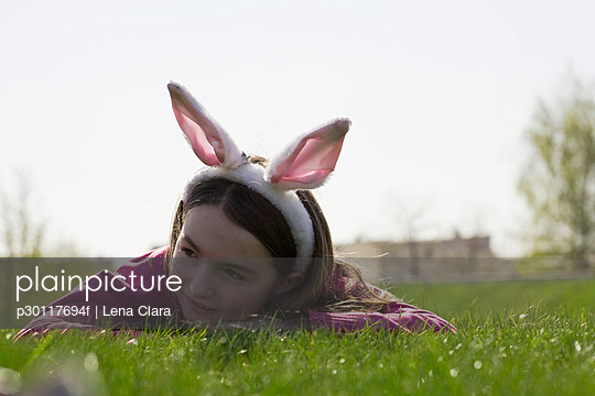 A girl wearing rabbit ears and lying down on grass