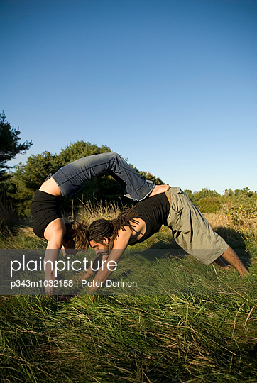 Man and woman practicing yoga in a field, Maine.