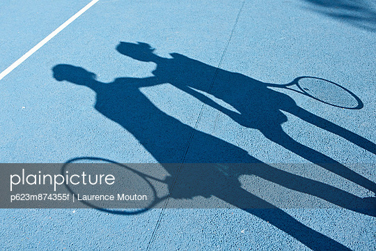 Shadow of tennis players on tennis court