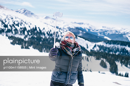 A woman on the ski slopes holding out her smart phone to take a photograph.