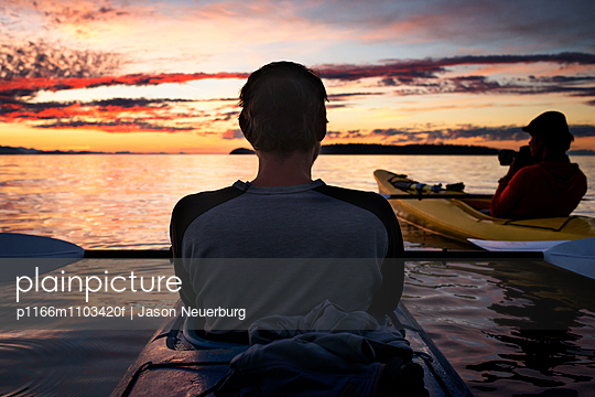 Rear view of man kayaking on lake at sunset