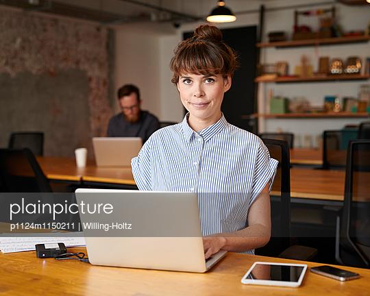 Junge Frau mit Laptop am Arbeitsplatz - p1124m1150211 von Willing-Holtz