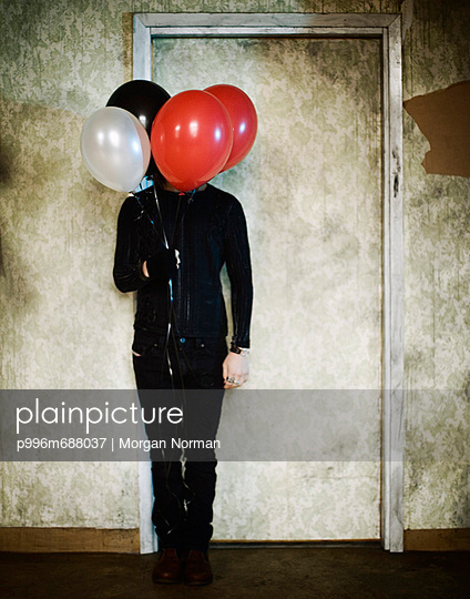 Man Carrying Balloons Covering His Face