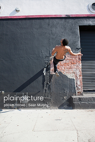 Man running up wall, demonstrating parkour