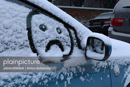 Sad face drawn in snow on car window