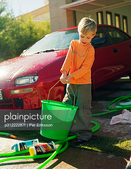 A boy washing a red car