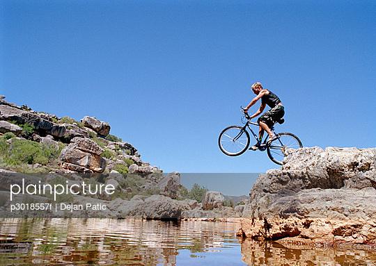 A man jumping a mountain bike into a stream