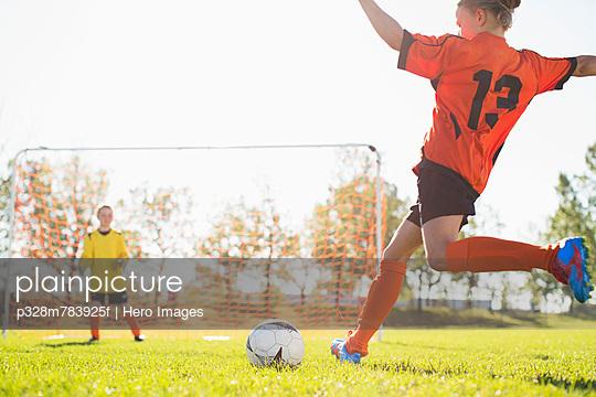 Female soccer player moving ball towards net.