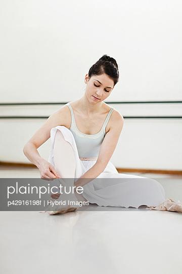 Ballet dancer tying her shoe in studio