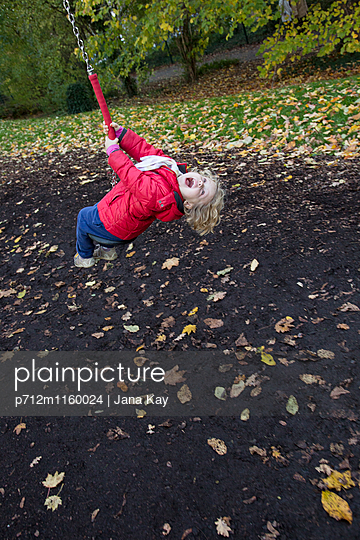 Kind spielt auf einer Schaukel - p712m1160024 von Jana Kay