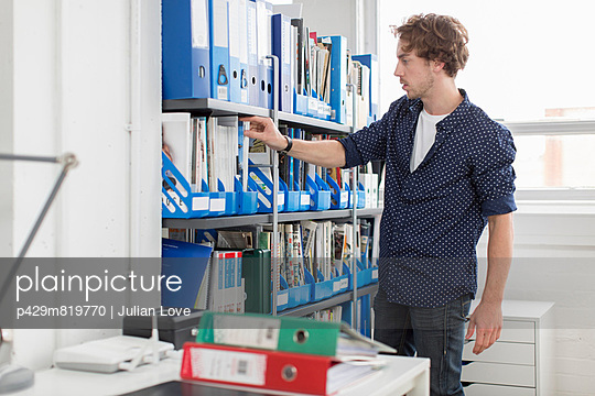Young office worker taking file from shelf