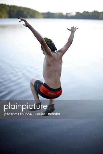 Junge springt in Goldensee, Haus Strauss, Bauernkate in Klein Thurow, Roggendorf, Mecklenburg-Vorpommern, Deutschland - p1316m1160534 von Hauke Dressler