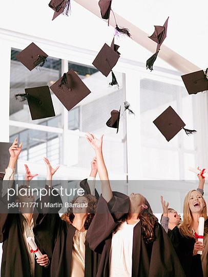 Graduates throwing mortarboards in air
