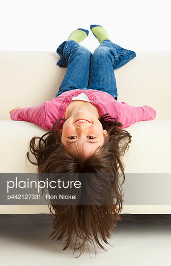 A Girl Hanging Upside Down From The Couch