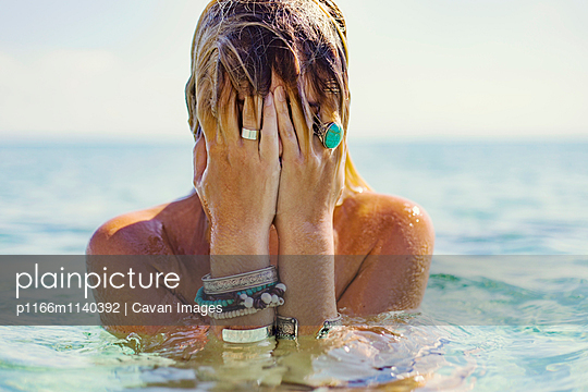 Close-up of wet woman covering face in sea