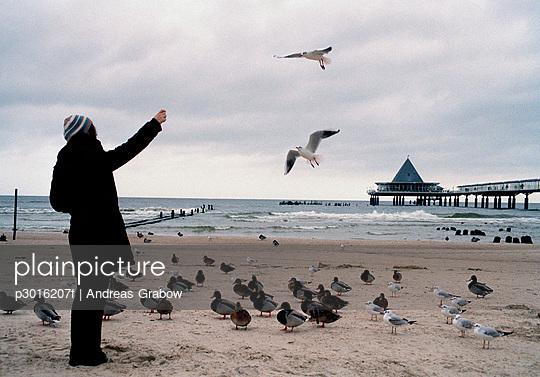 Woman feeding birds on a beach