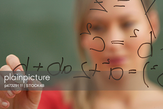 Woman is writing on an glass board