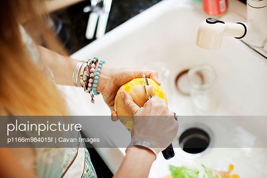 USA, New York State, Close-up of woman peeling apple above sink