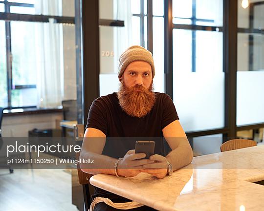 Mann mit Bart und Smartphone im Büro - p1124m1150250 von Willing-Holtz