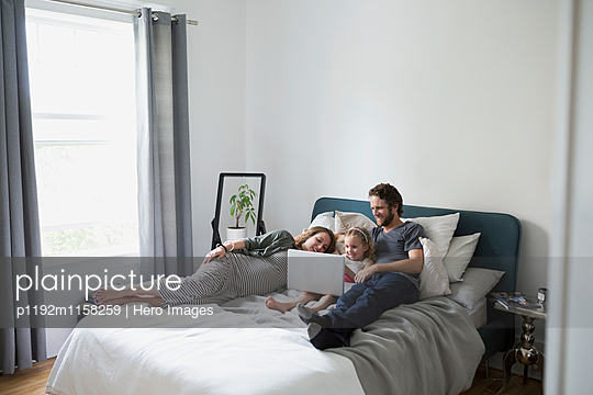 Young family using laptop on bed