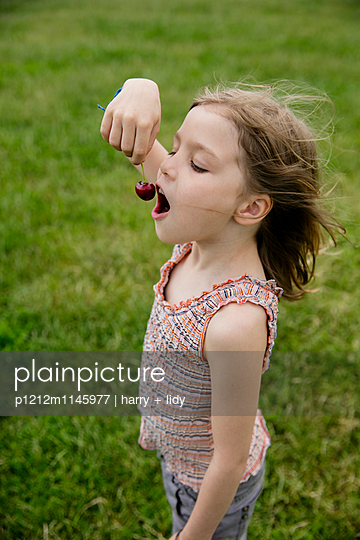 Mädchen isst Kirschen auf der Wiese - p1212m1145977 von harry + lidy