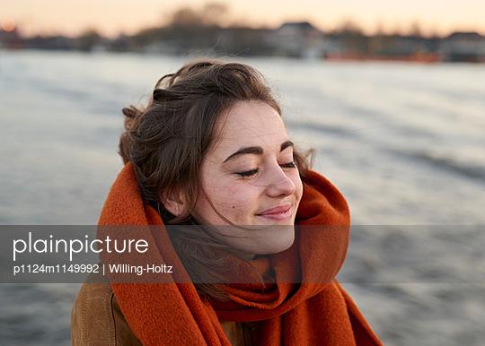 Junge Frau mit geschlossenen Augen am Wasser - p1124m1149992 von Willing-Holtz