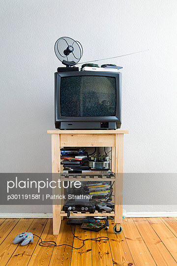 A television set on a cabinet with lots of DVDs and video games