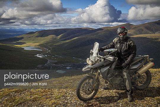 Adventure motorcyclist sitting on his BMW F800GS at the top of a hill off of the Denali Highway, Southcentral Alaska, Summer