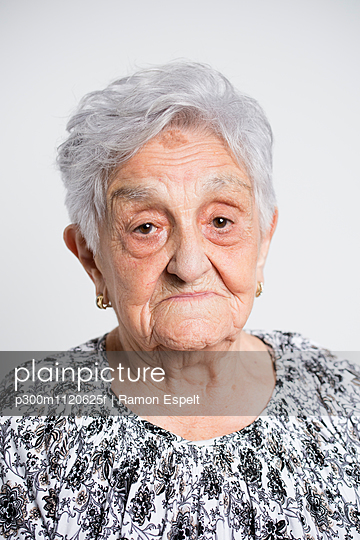 Portrait of sad senior woman in front of white background