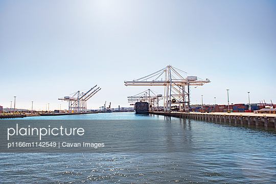 Scenic view of commercial dock at sea against sky
