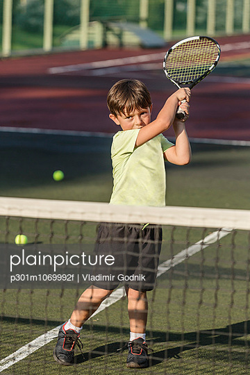 Boy playing tennis in court during sunny day