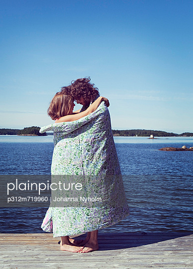 Couple wrapped in towel embracing on beach