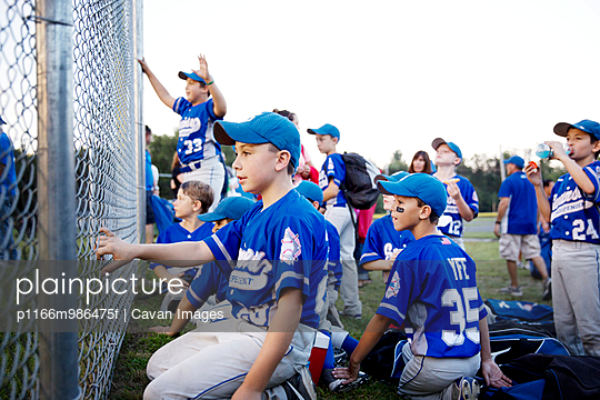 Little League Team Cheering from Behind Fence