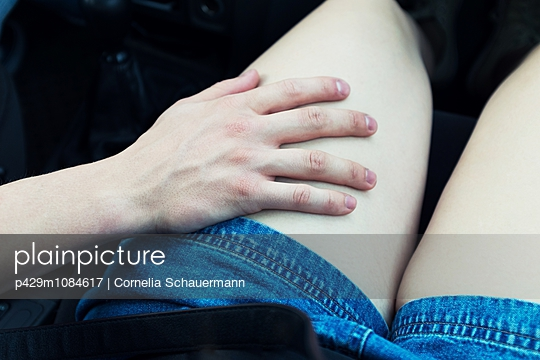 Young mans hand on young womans thigh