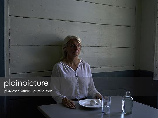 Ältere Frau sitzt am Tisch - p945m1163013 von aurelia frey