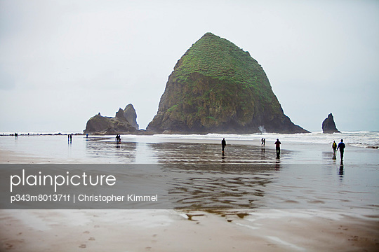 Several people enjoy the large sandy beach below a large rock.