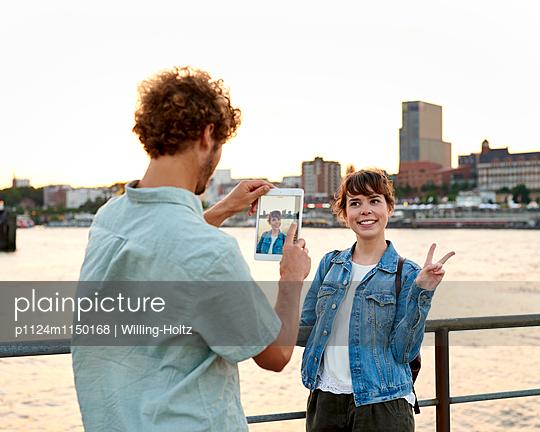 Mann fotografiert Frau mit Tablet an der Elbe - p1124m1150168 von Willing-Holtz