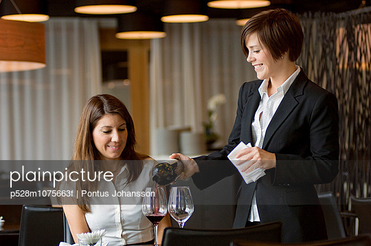 Waitress serving wine to woman at table, smiling