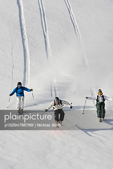 Three people skiing in line with tracks in the background