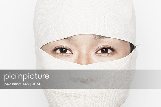 Woman with face bandaged, only eyes visible