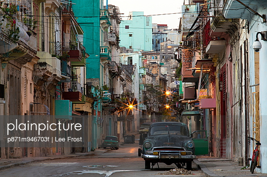 Street scene before sunrise showing dilapidated buildings crowded together and vintage American cars, Havana Centro, Havana, Cuba, West Indies, Caribbean, Central America