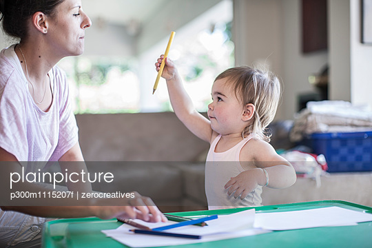 Mother and baby girl together at home drawing