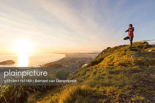 Eine Frau macht Yoga bei Sonnenaufgang auf dem Mount Maunganui, Nordinsel, Neuseeland - p1316m1161163 von Bernard van Dierendonck
