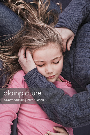 Young blonde girl lying in her mother\'s lap; hartford connecticut usa