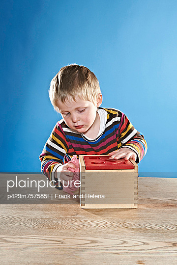 Boy cleaning wooden toy box