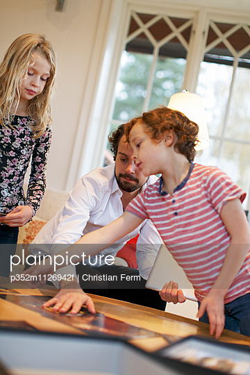 Sweden, Father and two children (6-7, 10-11) playing in living room