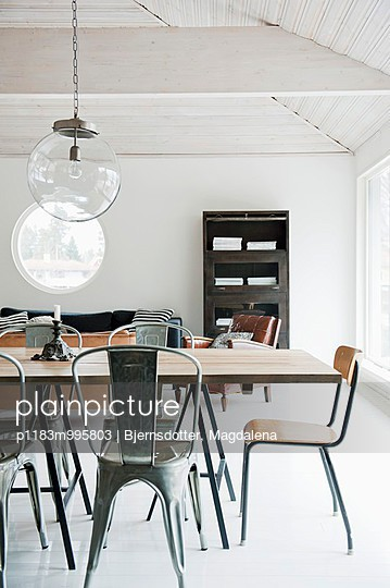 Minimalist, open-plan interior with industrial-style furniture; spherical glass lamp in front of porthole window of same size