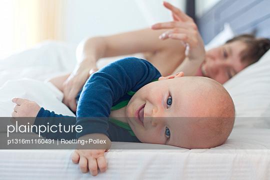 Baby liegt mit Mama im Bett, Rawai, Phuket, Thailand, Asien - p1316m1160491 von Roetting+Pollex
