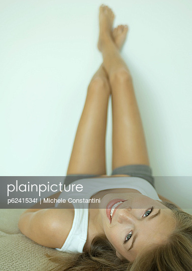 Young woman lying down with legs up